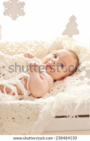 Cute little girl play with wood snowflakes toys in her cozy white bed - stock photo