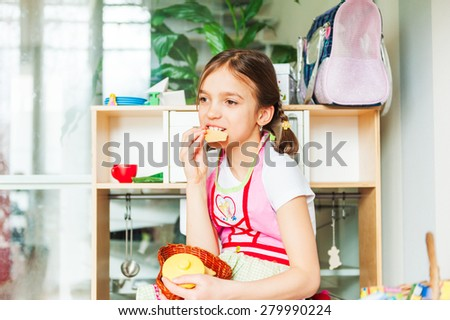 Cute little girl playing at home, eating cookies - stock photo