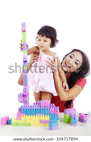 Cute little girl playing block with mother at home isolated on white