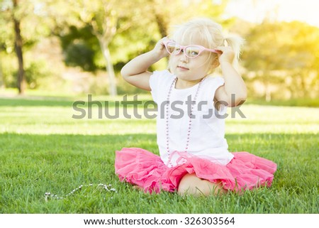 Cute Little Girl Playing Dress In The Grass Up With Pink Glasses and Beaded Necklace. - stock photo