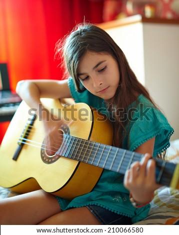 Cute little girl playing guitar indoor in her bedroom - stock photo