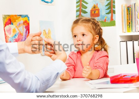 Cute little girl playing hand game with nurse - stock photo