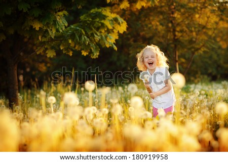 Cute little girl playing in a field. Spring field of dandelions. - stock photo