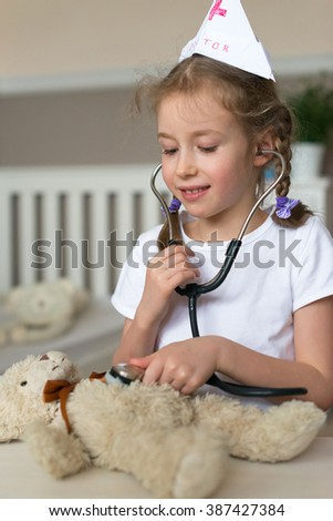 Cute little girl playing in doctor with her toy. - stock photo