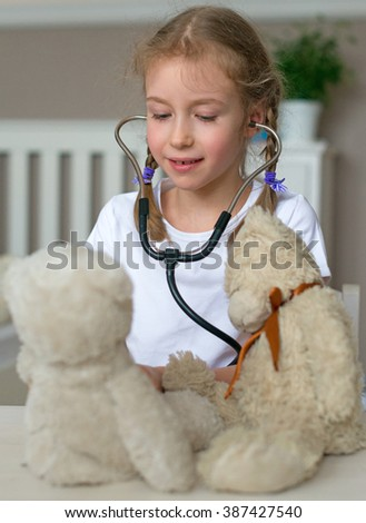 Cute little girl playing in doctor with her toys. - stock photo