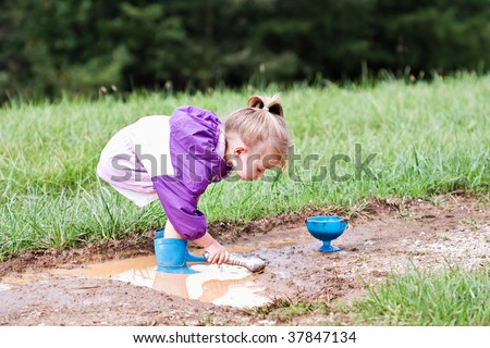 Cute little girl playing in the mud with ice cream scoops. - stock photo