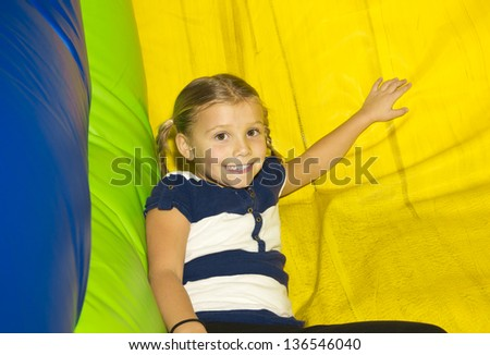 Cute little Girl playing on inflatable Side - stock photo
