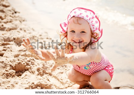 Cute little girl playing on the beach - stock photo