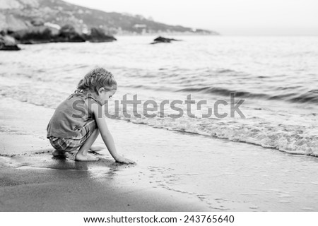 cute little girl playing on the beach at sunset ( black and white ) - stock photo