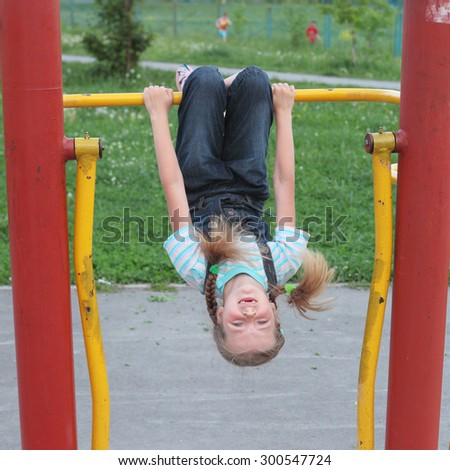 cute little girl playing on the playground outdoor