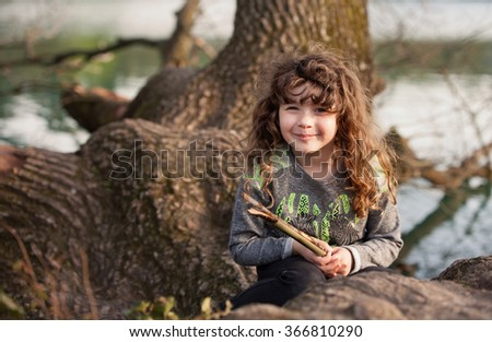 Cute little girl playing on the tree - stock photo