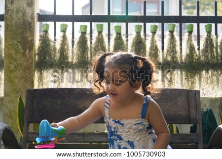 cute little girl playing soap bubbles with bubble gun on a sunny summer day.