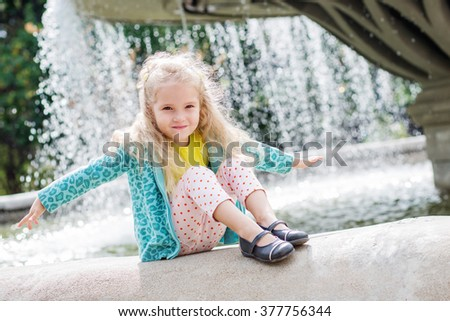 Cute little girl playing with a city fountain a sunny day - stock photo