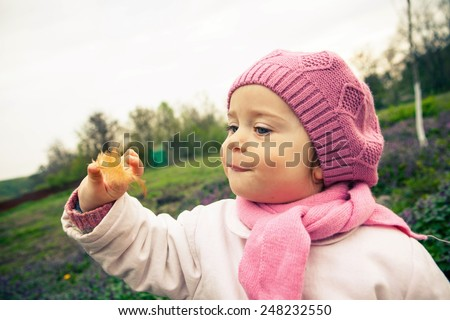 Cute little girl playing with a feather in a spring day outdoors, vintage color - stock photo
