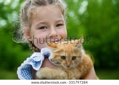 Cute little girl playing with a red kitten - stock photo