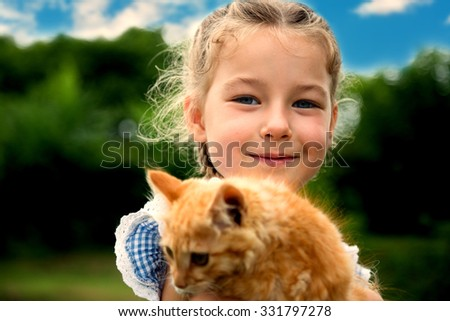 Cute little girl playing with a red kitten. Instagram style filtred image. - stock photo