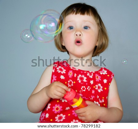 cute little girl playing with bubbles in the studio - stock photo
