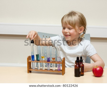 Cute little girl playing with chemistry; using different indicators (lakmus and BTB) to produce color reactions in acids and bases - stock photo