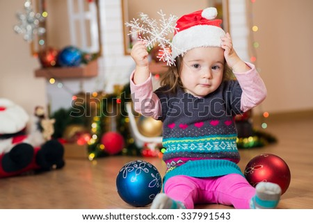 Cute little girl playing with christmas decorations