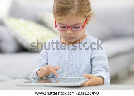 Cute little girl playing with digital tablet - stock photo