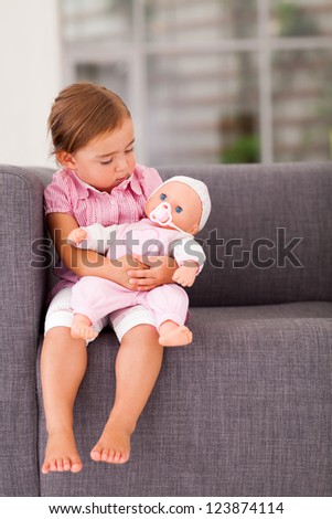 cute little girl playing with doll at home