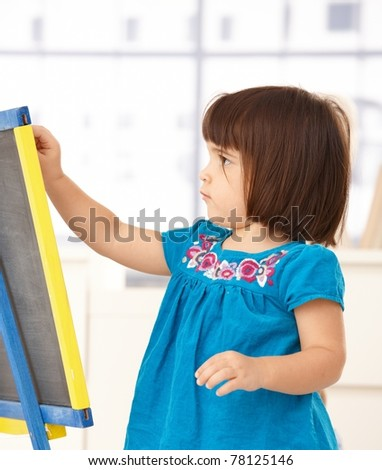 Cute little girl playing with drawing board, concentrating.?