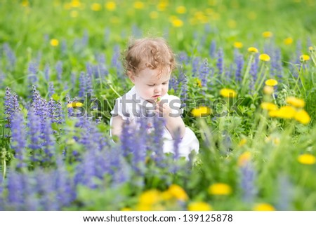Cute little girl playing with flowers in a garden