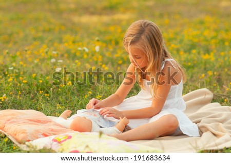 Cute little girl playing with her baby toy on the meadow on sunny spring day. - stock photo