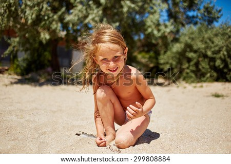 cute little girl playing with sand on the sunny beach