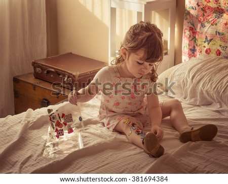 Cute little girl playing with stickers Kids Activity Stickers for Imaginative Play  - stock photo