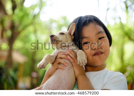 Cute little girl playing with thai dog, happy and smiling,asian child