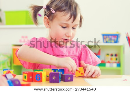 Cute little girl playing with toy bricks at school - stock photo