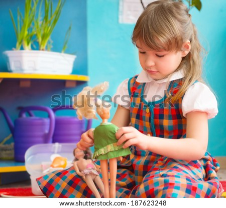 Cute little girl playing with toy doll at kindergarten