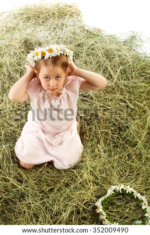 Cute little girl plays in the village on the haystack. She tries on a head a wreath of field daisies . Top view - Isolated on white background - stock photo
