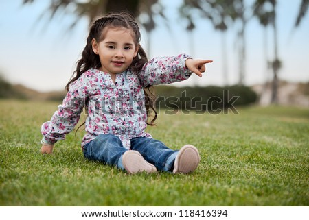Cute little girl pointing at something - stock photo