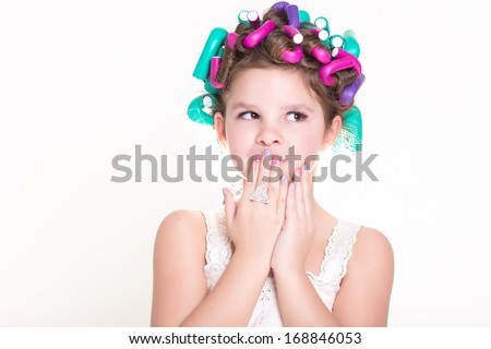 Cute little girl portrait in curlers and pajamas, skincare kid beauty and glamour. Funny baby girl with hair curlers. Lovely little girl smiling. Pajamas party.  Isolated, studio, white background.