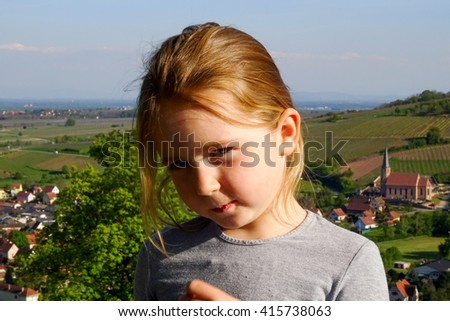 Cute little girl posing in countryside, sunny weather