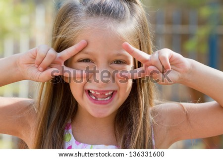 Cute little girl posing on the playground at bright summer day