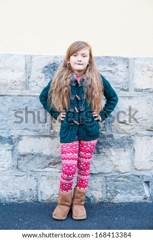 Cute little girl posing outdoors, wearing dark green cardigan, red and white pants and brown boots - stock photo