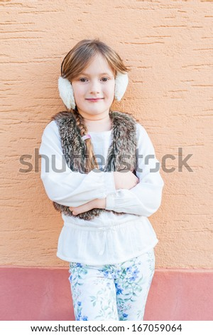 Cute little girl posing outdoors, wearing white blouse, faux fur vest, white printed jeans and earmuff