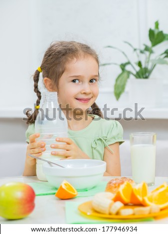 cute little girl pouring milk during breakfast of muesli with fresh fruits - stock photo