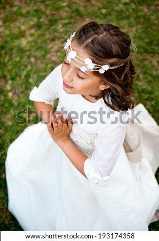 Cute little girl praying on the background of nature - stock photo