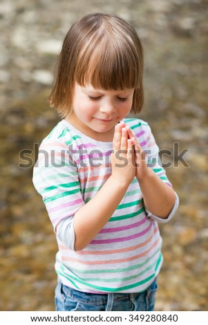 Cute little girl praying over textured background - stock photo