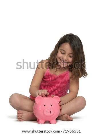 Cute little girl putting money in piggy bank - stock photo