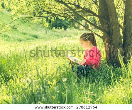 Cute little girl read the book under tree - stock photo
