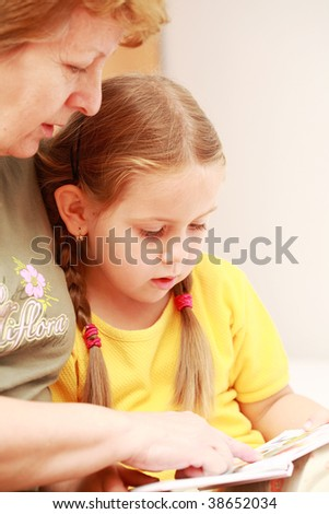Cute little girl reading a book with her grandmother - stock photo