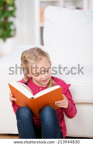 Cute little girl reading book in front of sofa at home