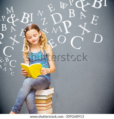 Cute little girl reading book in library against grey background