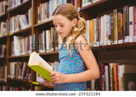Cute little girl reading book in the library - stock photo