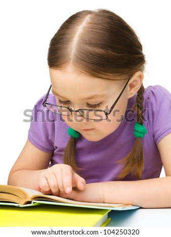 Cute little girl reading book wearing glasses, isolated over white - stock photo
